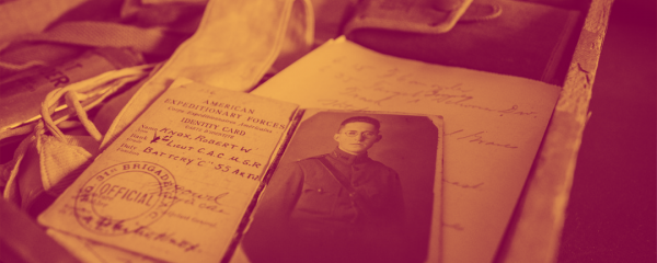 Archival documents like a passport, letters, and leather satchel