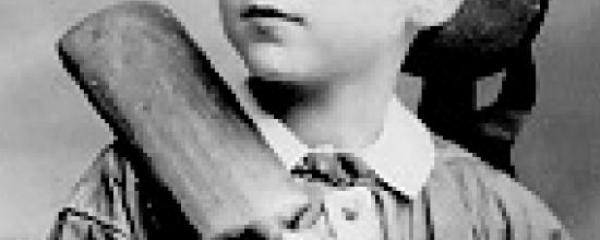 Shoulders and lower half of face of boy with cricket bat (formal portrait).